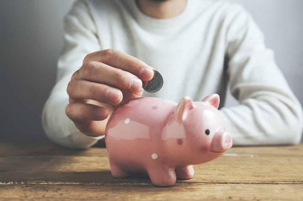 Pessoa colocando moeda no cofre de porquinho