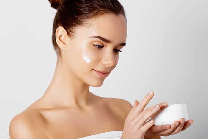 mulher hidratando a pele em casa